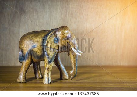 Handcraft wood elephant sculpture on wood background.