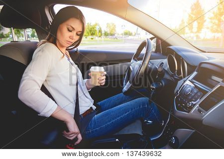 Young beautiful woman driving a car seat belt with a cup of coffee in hand