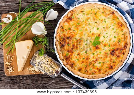 French onion cheese quiche or pie in a gratin dish on green table mat with grater and ingredients on cutting board authentic recipe view from above close-up