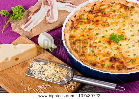 tasty quiche in gratin dish on magenta table mat with grater spring onion and cheese on cutting board authentic recipe view from above close-up