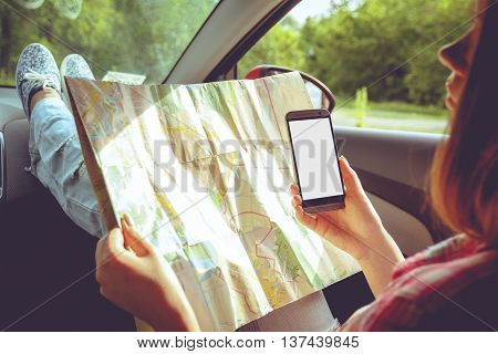 Girl with map and phone in hand in the car. Car travel, hitchhiking concept