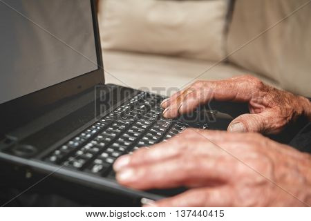 Senior sitting on the couch with a laptop in hand. mock up. Progressive elderly man