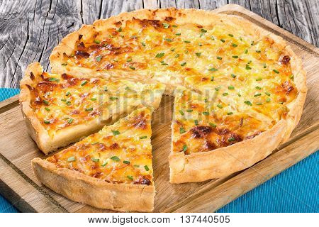 French onion cheese quiche or tart cut into pieces view from above close-up