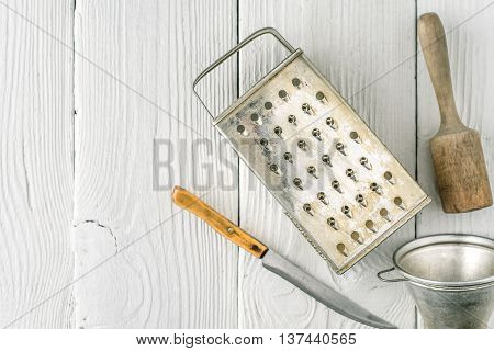 Grater plunger strainer and knife on the white wooden table top view