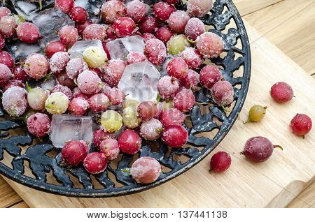 Frozen gooseberry with pieces of ice on a black vintage plate