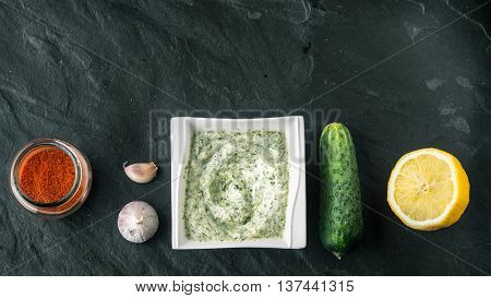 Tzatziki on the stone table with cucumber lemon and seasoning wide screen