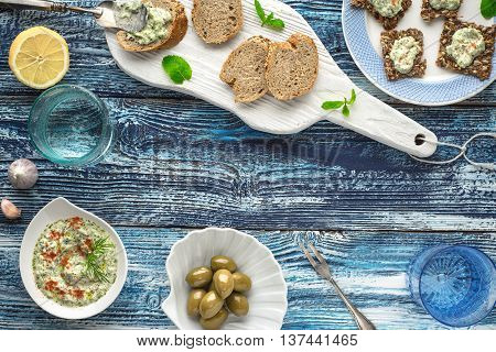 Bread with tzatziki on the blue wooden table with accessorize