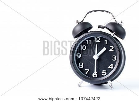 Black double bell alarm clock showing half past one on white background
