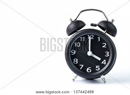 Black double bell alarm clock showing four o'clock on white background
