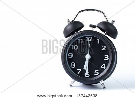 Black double bell alarm clock showing half past six on white background