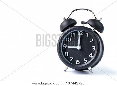 Black double bell alarm clock showing nine o'clock on white background