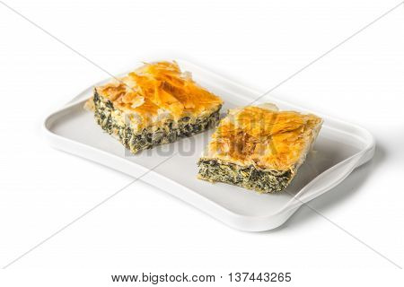 Piece of Greek pie spanakopita on the white plate on the white background