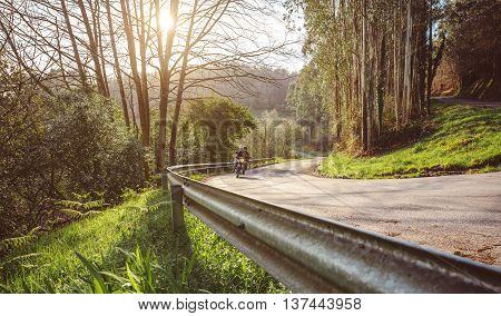 Senior couple riding a motorbike along forest road in autumn