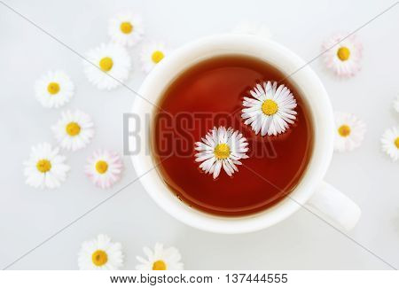 Cup of tea with camomile flowers. Shallow depth of field. Selective focus. Top view.