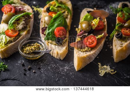 Slices of ciabatta with olives tomatoes and basil on the black stone table