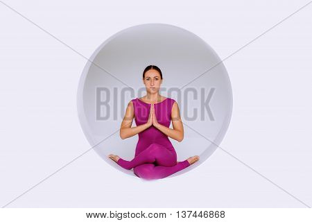 sporty woman in active wear practicing yoga exercises in geometric design of round shapesin sphere. Studio shot white background. Creative concept of sports.