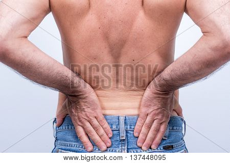middle-aged man with severe pain in the lumbar region pushes them with the hands