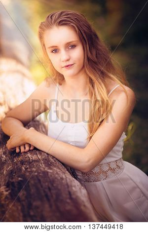 Beautiful teenage girl posing by log