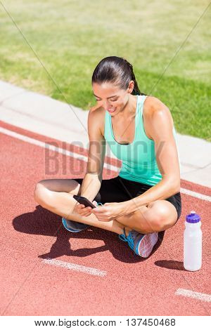 Happy female athlete using mobile phone on running track
