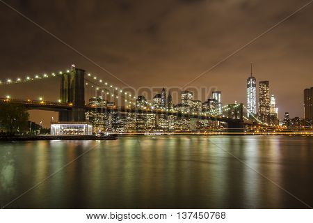 Brooklyn Bridge and downtown Manhattan during night time. Colorful reflections in the East River.