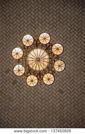 A beautiful vintage chandelier, an underneath view. Nice brick pattern.
