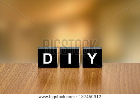 DIY or do it yourself on black block with blurred background