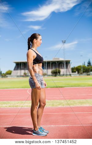 Female athlete standing on running track on a sunny day