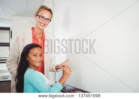 Teacher and pupil writing on whiteboard at school