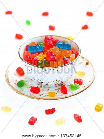 gummy bears candies in a bowl on white wooden background
