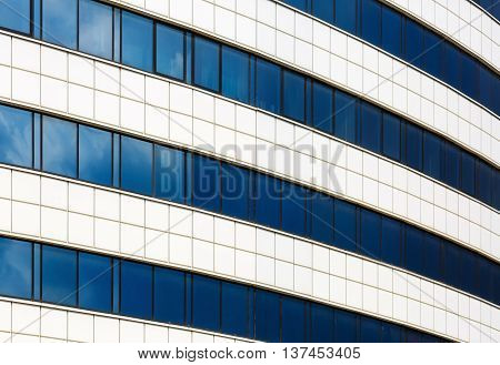 Facade of a modern building of steel and glass. Modern industrial architecture. Reflection of blue sky with clouds in the windows.