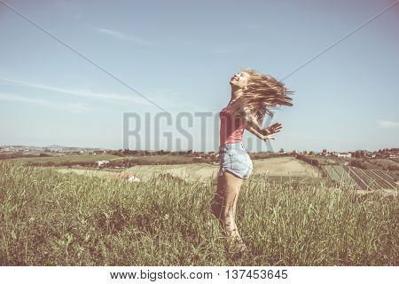 young woman enjoying freedom with open arms in a panoramic grass field - vintage style faded colors and haze added