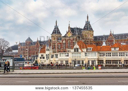 Amsterdam, Netherlands - April 2, 2016: Railway station and traditional old houses in Amsterdam, Netherlands