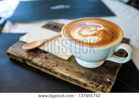 Latte Art Coffee Cup On Wooden Plate