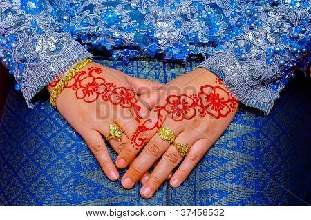 Henna Malay bride beautifully carved with wedding ring and gold bracelet.
