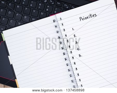 Handwriting Priorities on notebook with laptop keyboard in top view