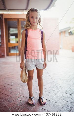 Front view of a cute little girl holding a lunch bag in front of her school