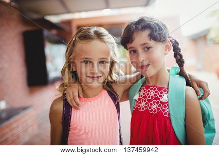 Two cute kids with arms around each other during the first day of school