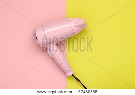 Pink hair dryer on pink and yellow paper background