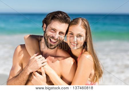 Portrait of romantic couple embracing each other on beach