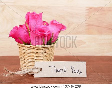 Closeup pink rose flower in the basket and handwriting Thank You on brown label paper with dark wood background