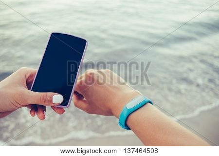 Female hands receive data from smart bracelet on a mobile phone on the beach. Toned image copy space.