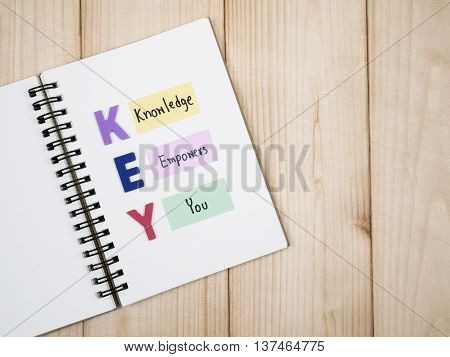 Word spell KEY and handwriting word Knowledge Empower You on notebook