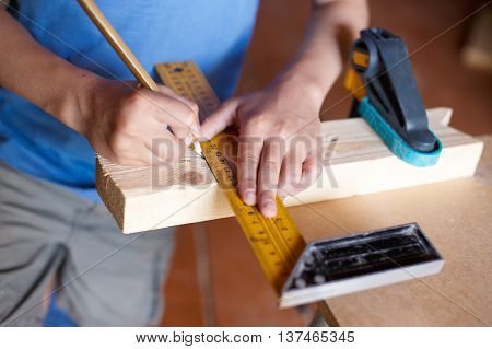 child measuring wooden bar and outlines where to saw off. Boy draws a line on the wooden material to accurately plan for future crafts