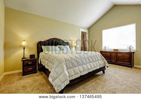 Master Bedroom With Deep Brown Furniture Set And Vaulted Ceiling.