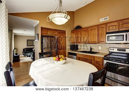 Cozy kitchen and dining room interior with vaulted ceiling. Furnished with black table set brown cabinets and built-in stainless steel fridge. View of living room