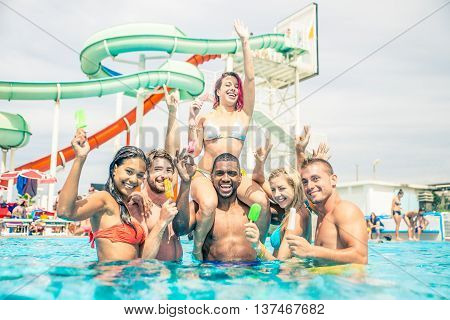 Group of friends having fun in a waterpark - Young people enjoy summer holiday