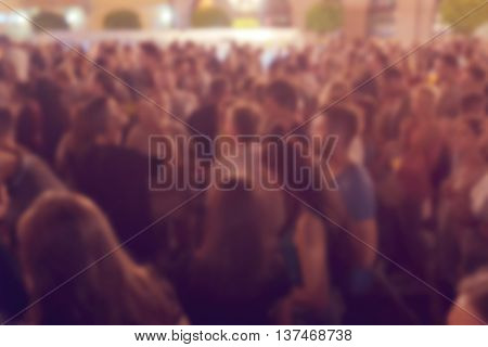 Unrecognizable crowd of young people at outdoor summer night party defocussed blur youth as background