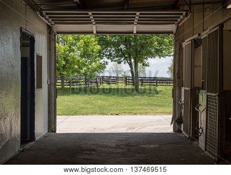 Empty Stables leading to horse fields green in summer