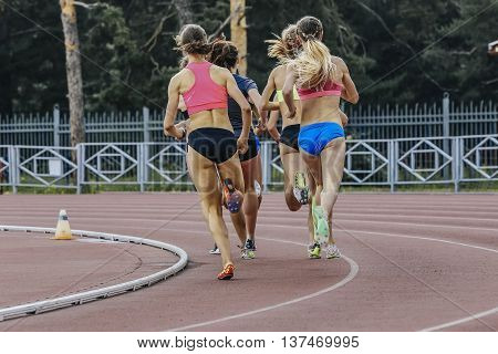 group of women athletes running in stadium during athletics competitions