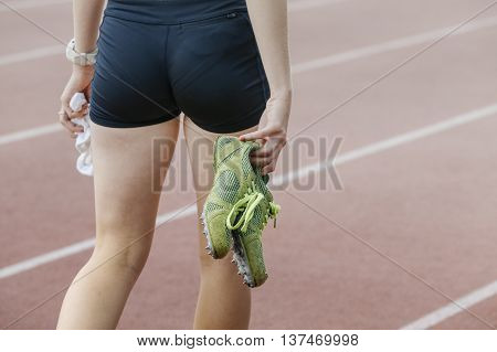 girl athlete is in hands spike running shoes after sprint race